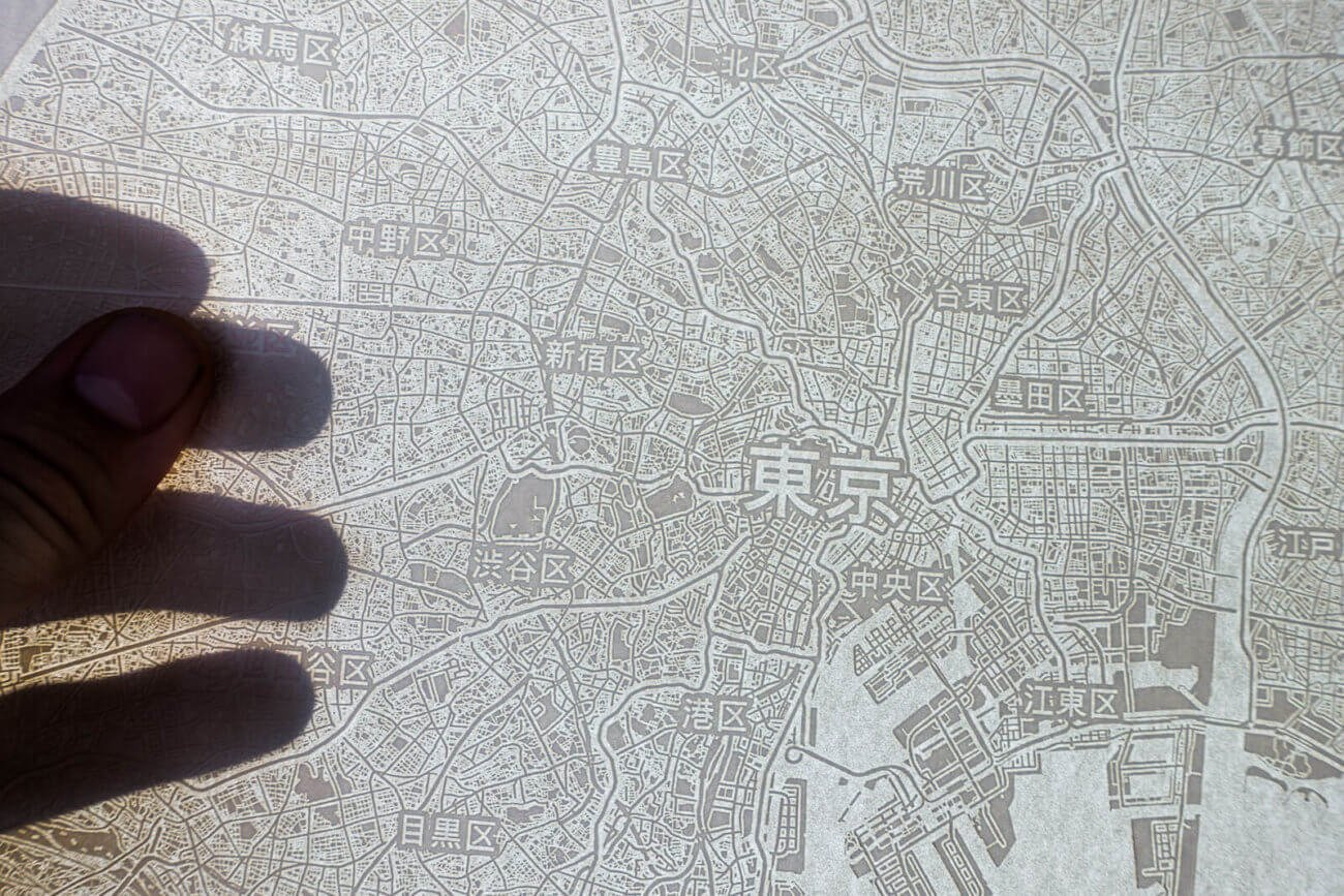 Light shines through the engraved paper map of Tokio